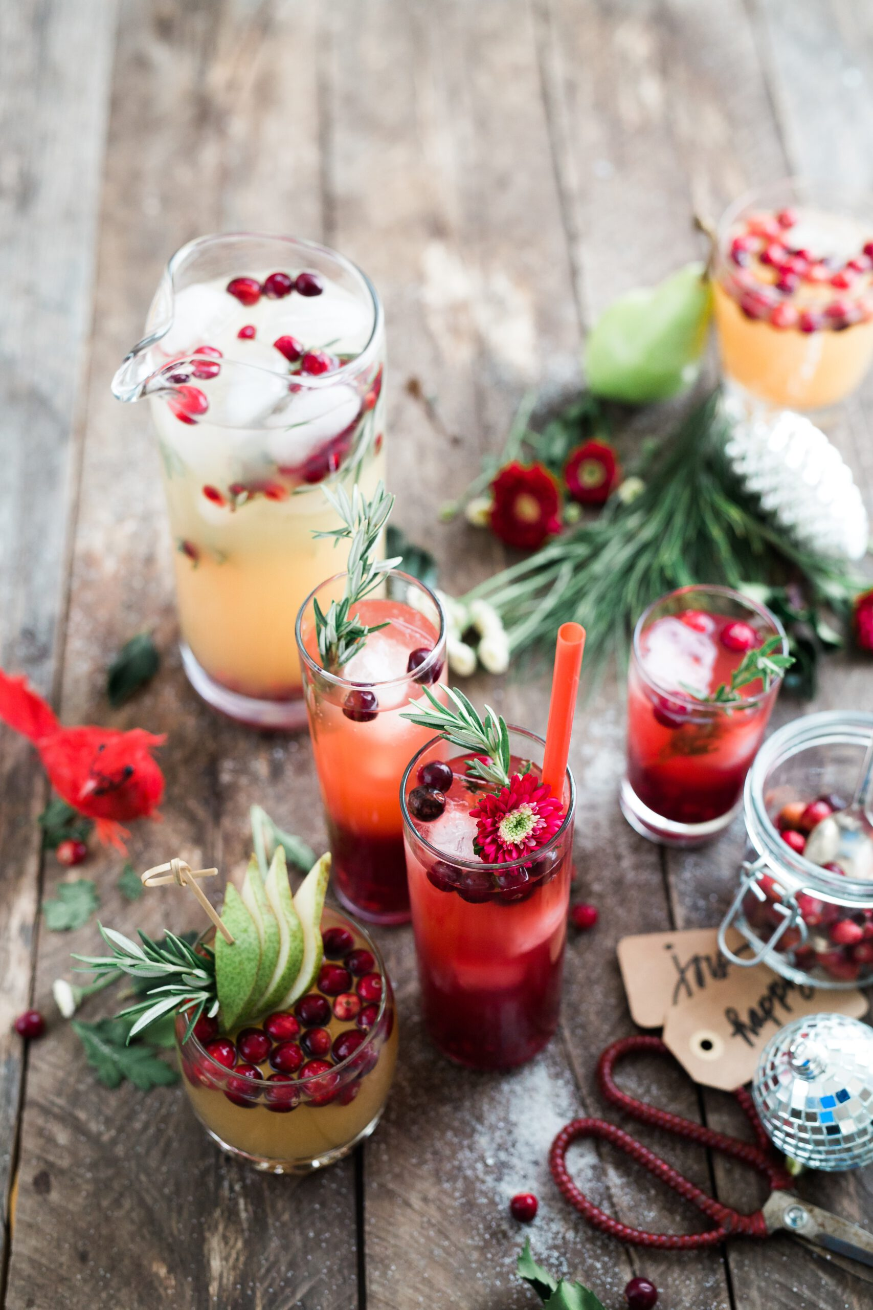 red drinks and cocktails on a wooden table with christmas decoration